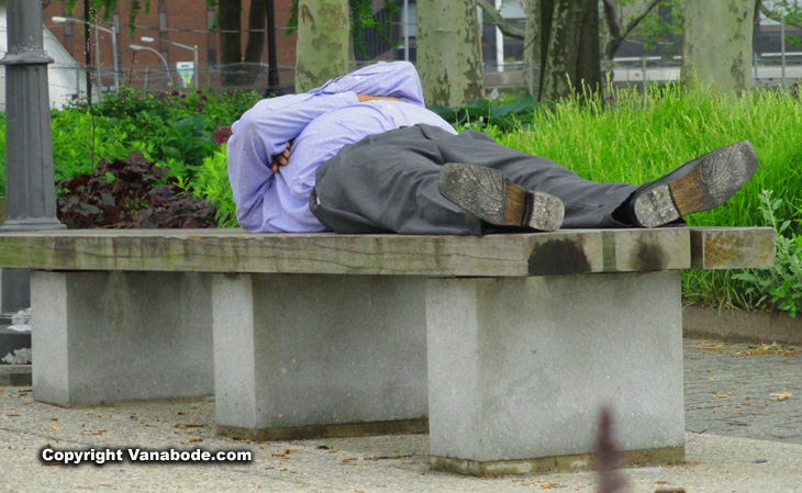 man sleeping on bench in new york city